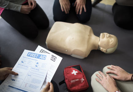 First aid class with CPR dummy and handouts.