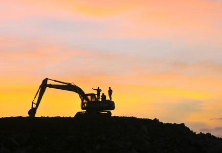 Sunset view of heavy construction equipment in use at a construction site.